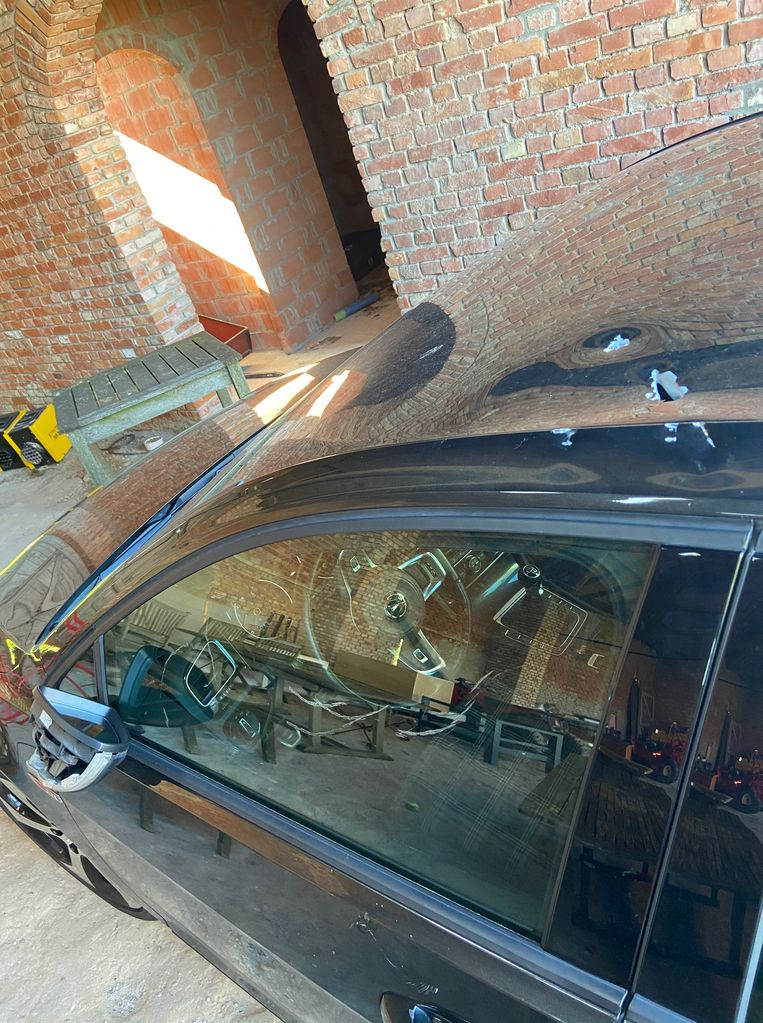 De gaten in het koetswerk van de VW Golf van Tristan. Ook het raam is beschadigd.