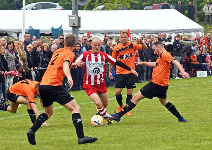Bob Hubregtse van Sluis wurmt zich door een woud van spelers van Nieuw Borgvliet. Op de achtergrond staat de feesttent klaar.