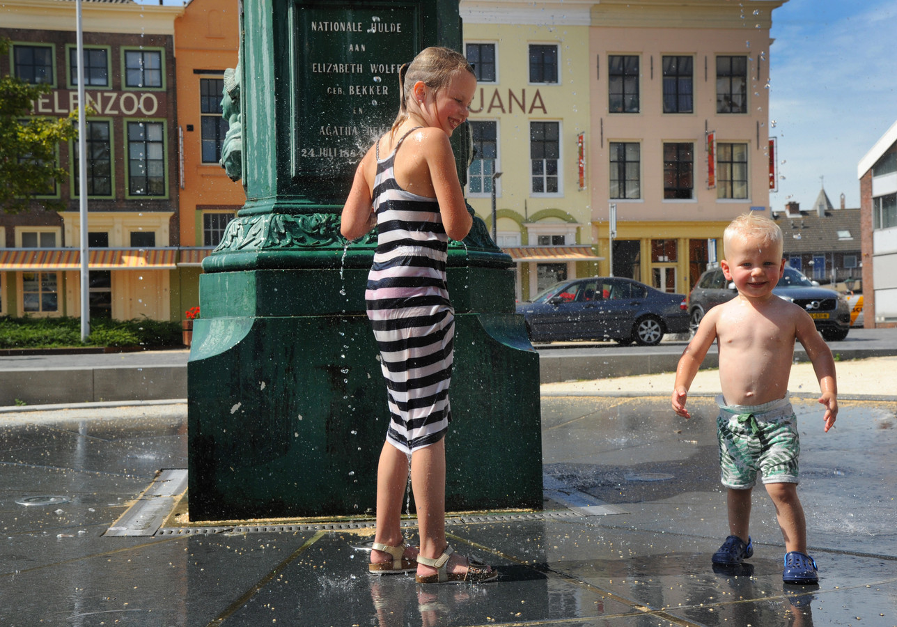 Nadia Smaardijk en haar broertje Levi zoeken verkoeling bij de Betje Wolff-fontein op het Bellamypark in Vlissingen.