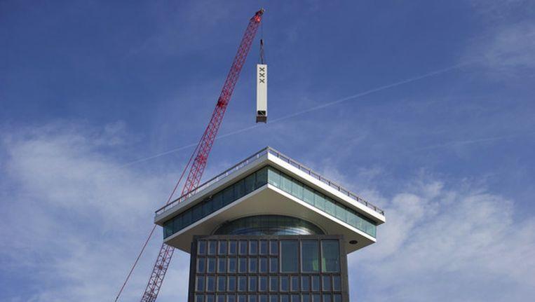 Precisiewerk van een kraanmachinist was gisteren te zien op de noordelijke IJoever: de plaatsing van een vijftien meter hoge windvaan op de A'dam Toren. Beeld Jasper Juinen