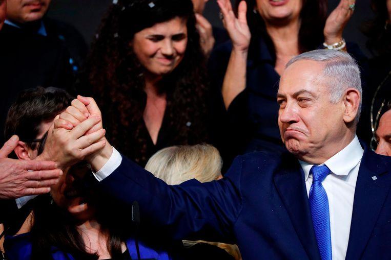 De Israëlische premier Benjamin Netanyahu schudt handen met aanhangers na zijn overwinningstoespraak in Tel Aviv.  Beeld AFP