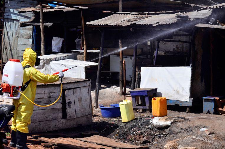 Een Oegandese gezondheidsmedewerker desinfecteert een openluchtmarkt in Kampala. Beeld REUTERS