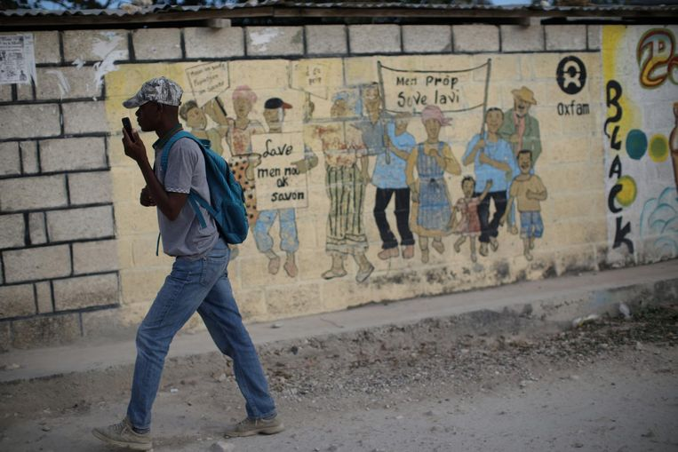 Een man loopt langs een muurschildering van Oxfam in het Haïtiaanse Corail, waar veel mensen een onderkomen moesten vinden na de aardbeving in 2010. Beeld null