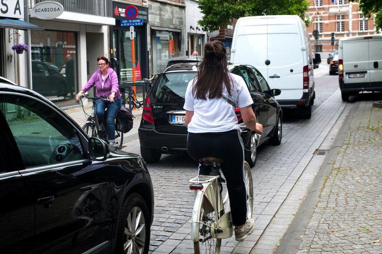 Auto's rijden rakelings deze fietsster in de Strijdersstraat voorbij , terwijl er verderop een bestelwagen op het voetpad staat geparkeerd.