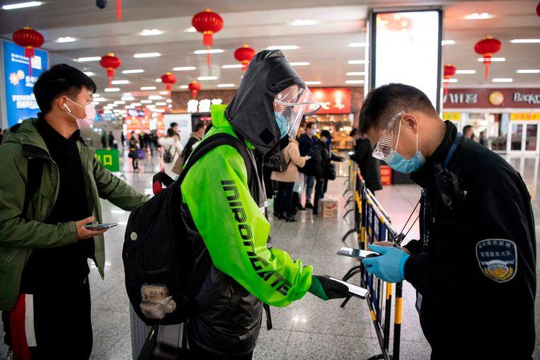 Een passagier met gezichtsmasker toont zijn groene QR-code op een treinstation in Wenzhou: hij vormt een laag risico. Beeld null