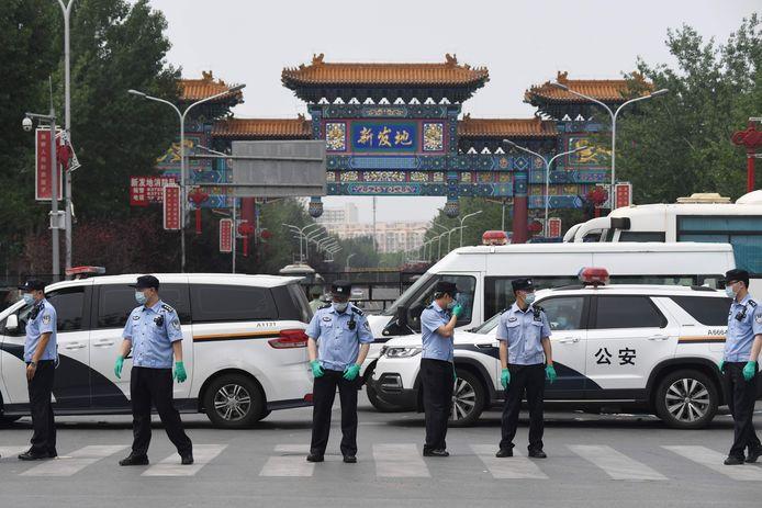 Chinese politieagenten bewaken de ingang van de Xinfadi-markt in Peking