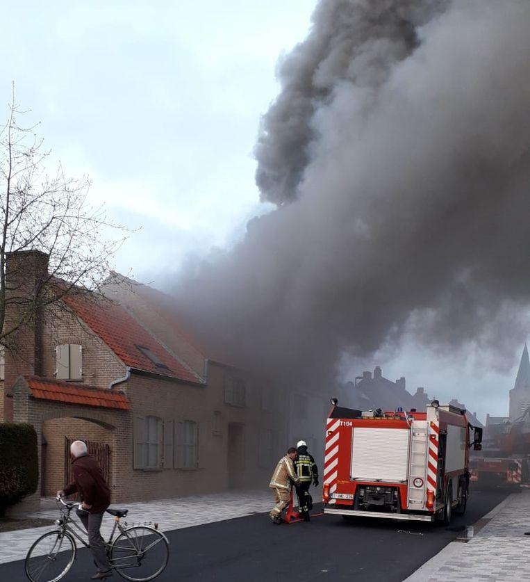 De woningbrand zorgde voor een enorme rookpluim. Ook het huis van de buren liep rookschade op.