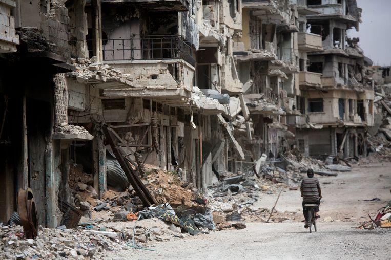 Een man fietst door een kapotgeschoten wijk van Homs. Beeld ap