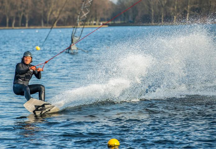 Een man wakeboardt op de Zegerplas in Alphen op de eerste lenteachtige dag van dit jaar.