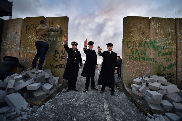Leden van 'grensinwoners tegen de Brexit' spelen dat de harde Ierse grens is hersteld.  Beeld Getty Images