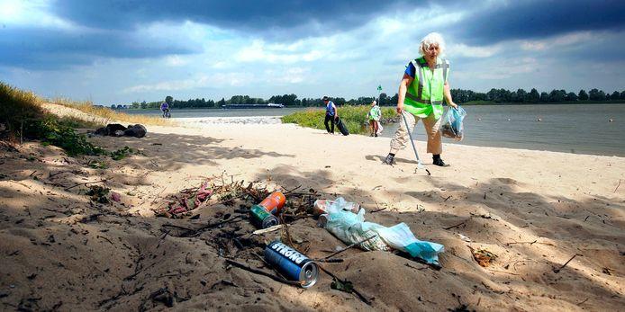 Vrijwillige opruimers rapen blikjes, sigarettenpeuken en gebruikte babyluiers op bij het strandje van Woudrichem.