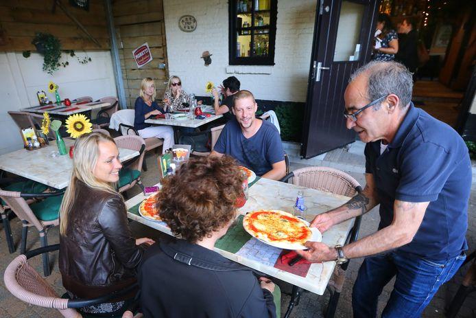 Gianni Delogu serveert pizza uit op het terras van La Pergola in Baarle-Nassau. Foto: Ramon Mangold/ Pix4Profs