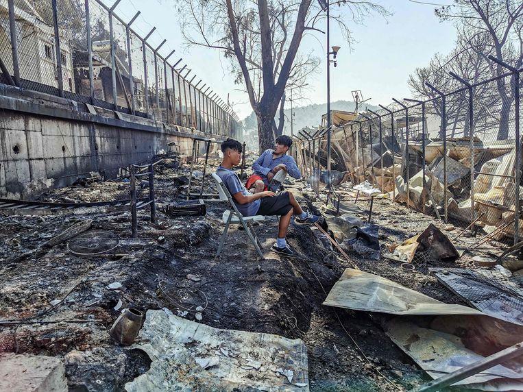 Migranten zitten in een afgebrand gedeelte van vluchtelingenkamp Moria op het Griekse eiland Lesbos. Beeld AFP