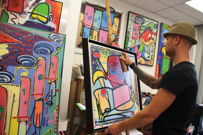 Beeldend kunstenaar Benjamin Scheltema toont een van zijn kleurrijke werken in zijn atelier in Roosendaal.