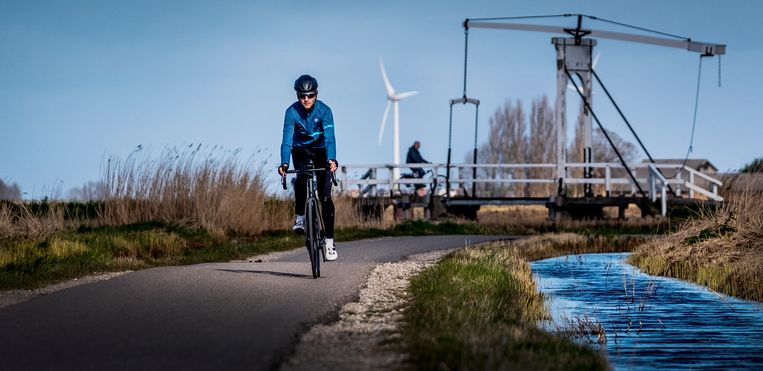 Kick Hommes, sportredacteur van Trouw, oplettend op de racefiets in de polder van Waterland. Beeld Patrick Post
