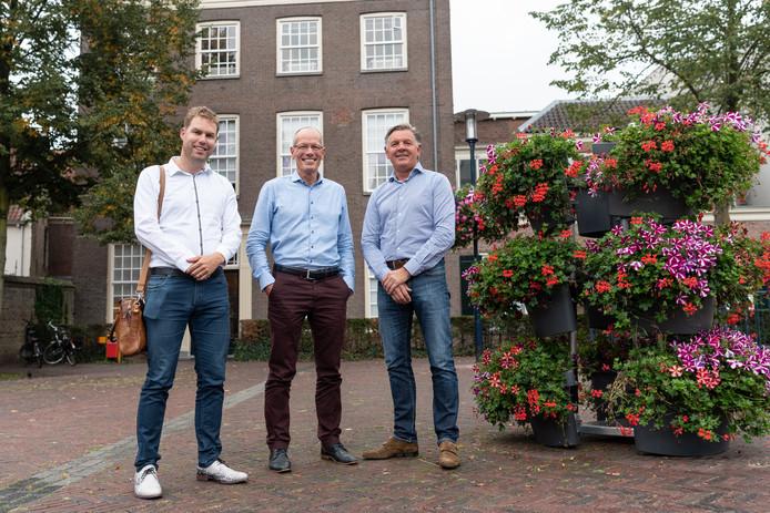 Maikel Gijzen, Walrick Halewijn en Gert-Jan Kreikamp (vanaf links) bij bloembakken die het centrum aankleden.