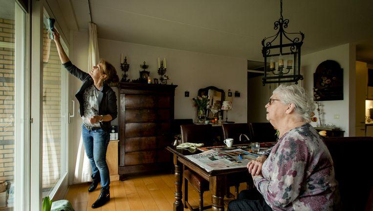 Een medewerkster van thuiszorgorganisatie Buurtzorg verzorgt de woning van mevrouw De Jong. Beeld anp