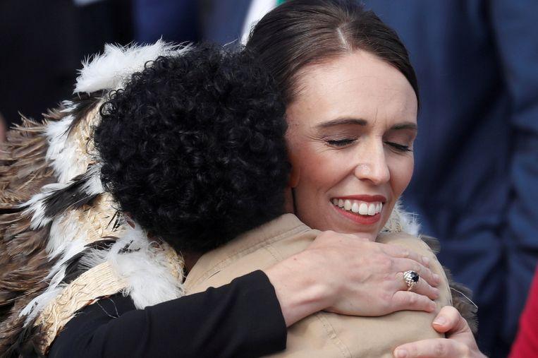 De Nieuw-Zeelandse premier Ardern omhelst een familielid van een dodelijk slachtoffer in Christchurch tijdens de herdenkingsceremonie.