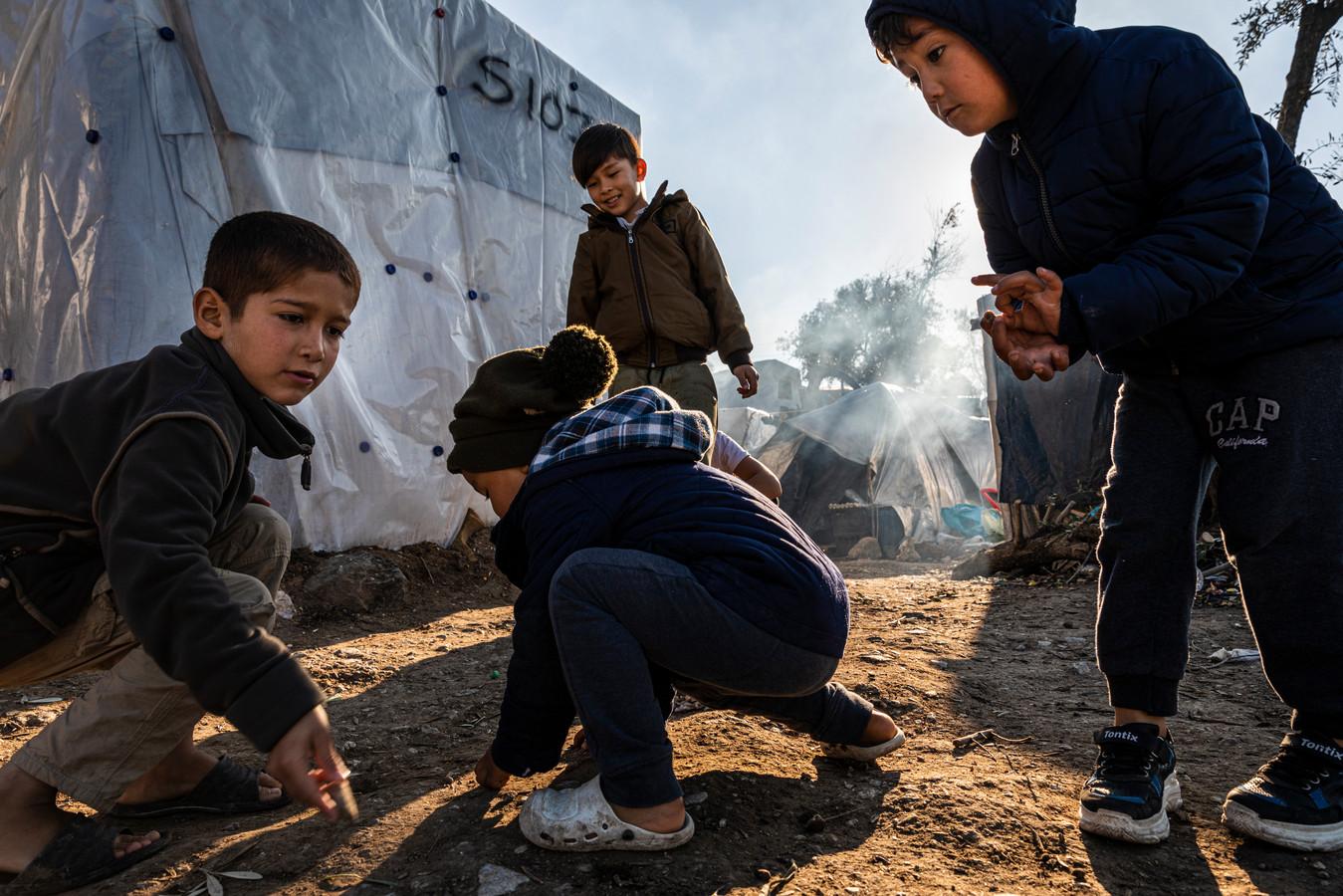 Griekenland, Lesbos, Kamp Moria. Momenteel zitten er naar schatting meer dan 20.000 vluchtelingen op het Griekse eiland Lesbos. Kinderen zijn aan het spelen met knikkers.