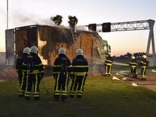 Smeulende vrachtwagen met hooi langs A27 bij Werkendam