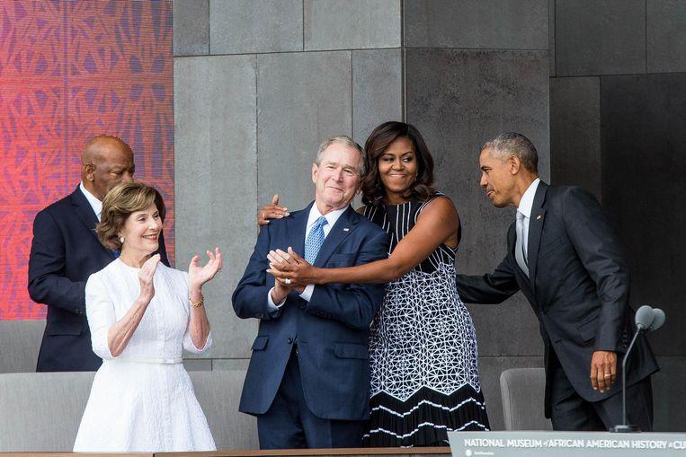 Michelle Obama houdt oud-president George W. Bush inning vast bij de opening van het Museum van Afro-Amerikaanse Geschiedenis in Washington. Beeld AFP