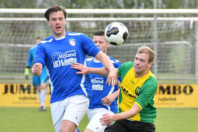 Paul Eshuis van DSVD (blauw) in duel met WVV'34-speler Wouter Hostink.