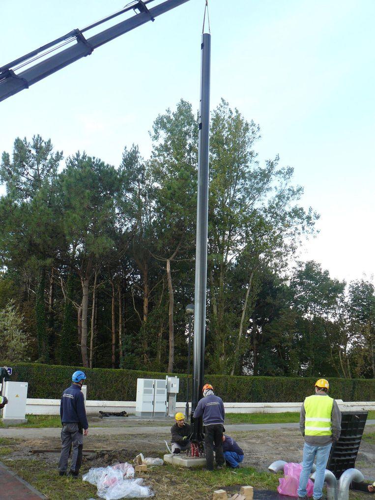 Arbeiders installeren de verlichtingspaal.