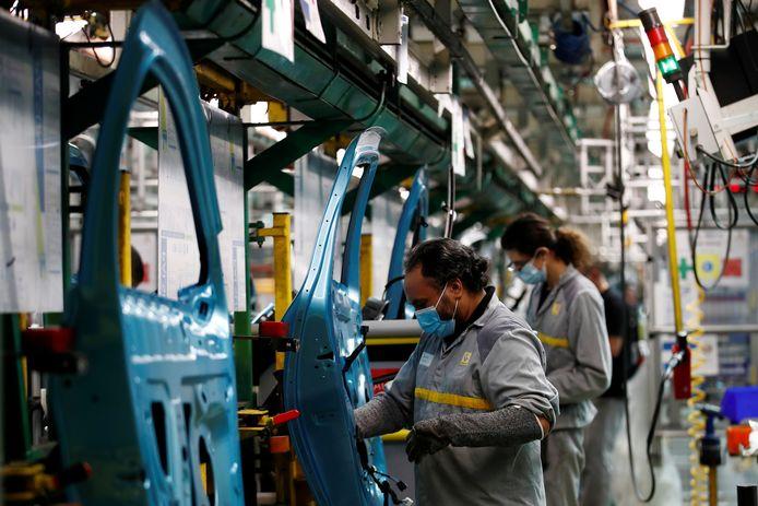 Renault-medewerkers met mondmaskers aan het werk in de fabriek van Flins in de omgeving van Parijs. Het is de grootste vestiging van het Franse automerk.