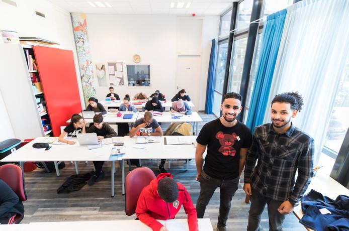 Danin El Houfi (l) en Nadir tijdens de huiswerkbegeleiding die zij aan kinderen geven.