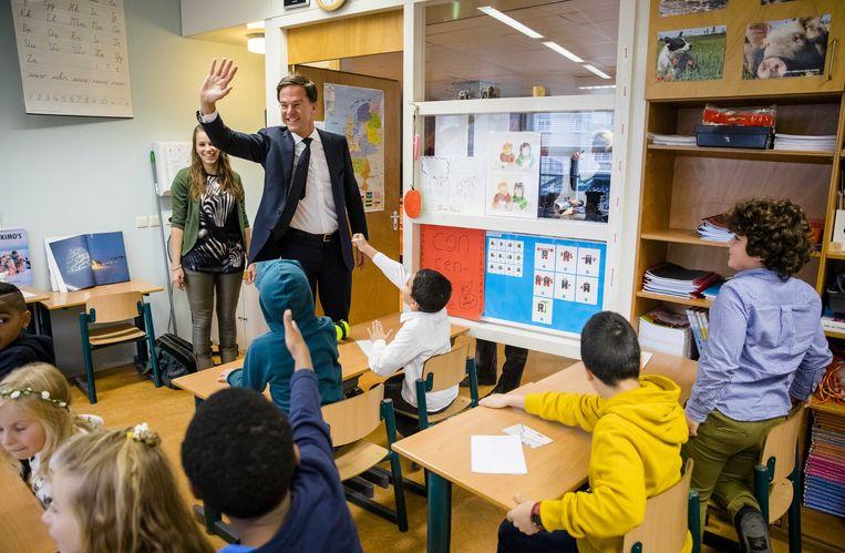 Mark Rutte woont een les burgerschapsonderwijs bij in Den Haag. Beeld ANP