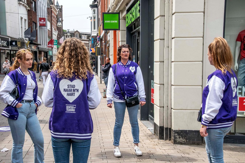 Gastvrouwen in paarse jasjes moeten ervoor zorgen dat het winkelend publiek in Tilburg voldoende afstand houdt. Luciënne Voets (derde van links) instrueert de andere gastvrouwen.