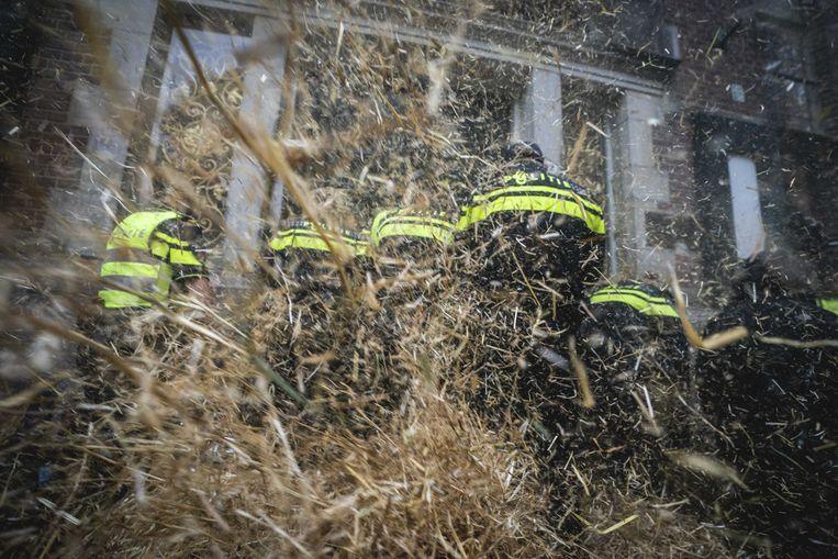 Politieagenten worden belaagd met stro tijdens het boerenprotest voor het provinciehuis in Groningen. Beeld Siese Veenstra, ANP