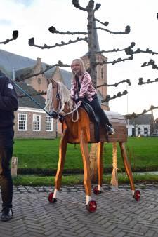 Kany (8) galoppeert op haar levensgrote houten paard door Dreischor