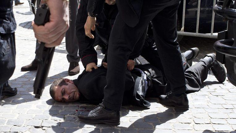 De schutter wordt gearresteerd voor het kantoor van de nieuwe Italiaanse premier in Rome. Beeld EPA
