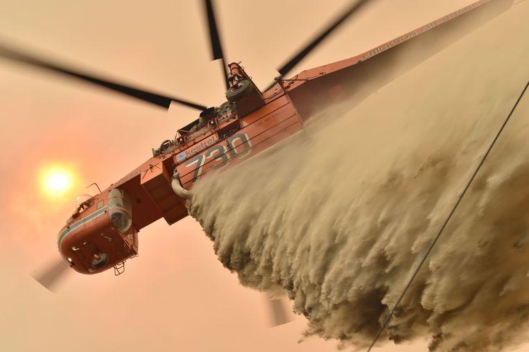 Een helikopter probeert een gebouw te redden van de vlammenzee in Balmoral, ten zuidwesten van Sydney.  Beeld AFP