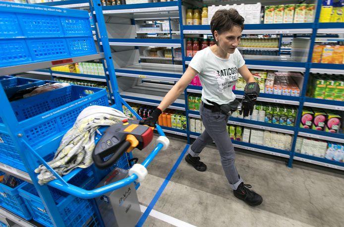 Een medewerkster van het Albert Heijn Home Shop Center is bezig om de bestellingen van klanten uit de lange stellingen te verzamelen.