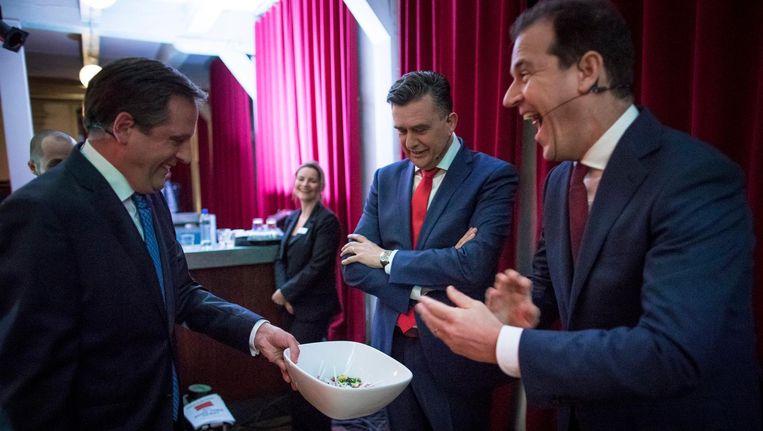 Alexander Pechtold biedt Emile Roemer en Lodewijk Asscher een lolly aan (als knipoog naar de foto waar Rutte en Roemer een drankje drinken tijdens een eerder debat in de Rode Hoed) tijdens de reclame van het Rode Hoed Debat. Beeld Freek van den Bergh / de Volkskrant