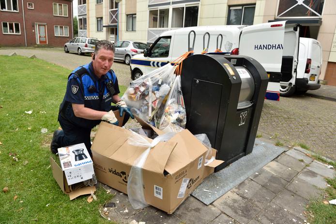 Gemeentemedewerker Marcel van de Loo zoekt naar een adres in verkeerd aangeboden afval in Gouda, om een boete uit te kunnen delen.