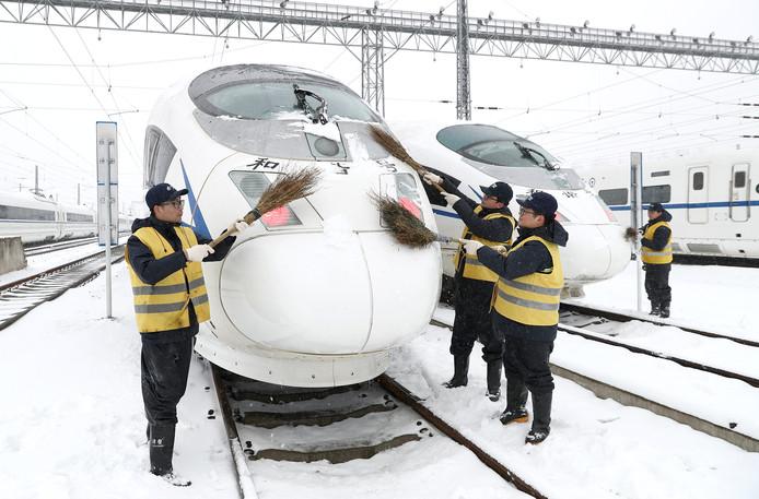 Chinees spoorwegpersoneel veegt de neus schoon van de hogesnelheidslijn bij een tussenstop in Hefei. Door de sneeuw heeft het spoorwegvervoer in sommige delen van China te kampen met vertragingen of uitval van treinen. Foto Guo Chen/Xinhua