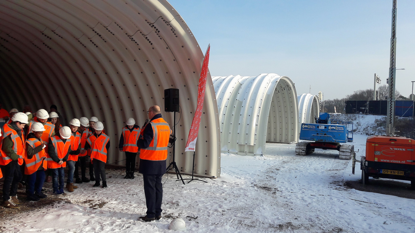 Leerlingen van groep 8 van De Blokkendoos trappelen van ongeduld in de sneeuw totdat wethouder Gerard Bruijniks is uitgesproken. De drie losse delen van de fietstunnel zijn afgelopen weken met 12.000 bouten in elkaar gezet.