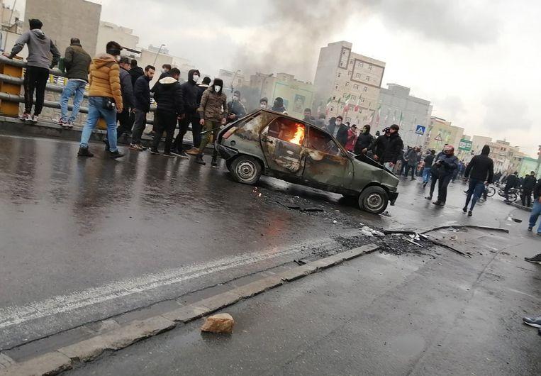 Demonstranten verzamelen zich rond een brandende auto tijdens protesten in Teheran, nadat de regering de benzineprijs fors heeft verhoogd. Beeld null