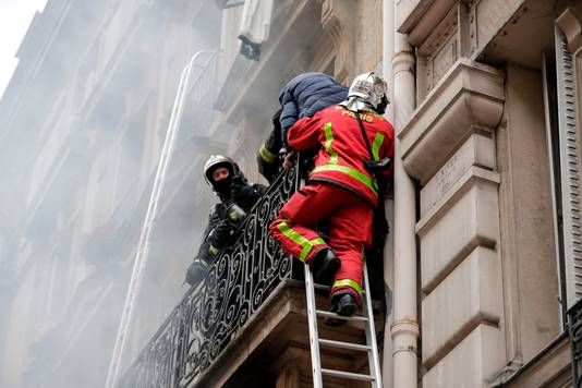 Bewoners boven de bakkerij worden met ladders omlaag geholpen.