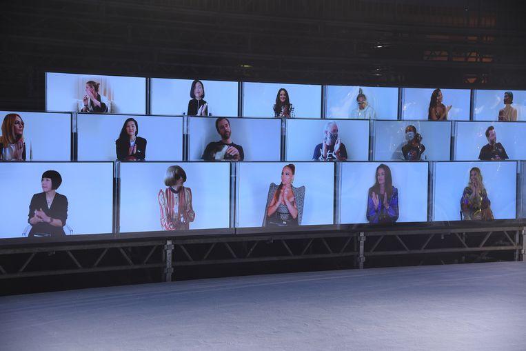 Celebrity's, vooraf opgenomen, waren tot hilariteit van de mensen bij de Balmainshow op deze manier toch een beetje aanwezig. Beeld Getty Images