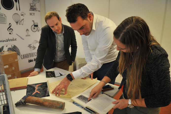 Joeri  van Kalleveen van Vilente (midden) buigt zich met Jasper Mous (links) en Janna Tiemersma over bijzondere historische documentatie over Mooi-Land. Op de voorgrond de loden koker met de oorkonde die achter de eerste steen van Mooi-Land verborgen bleek.