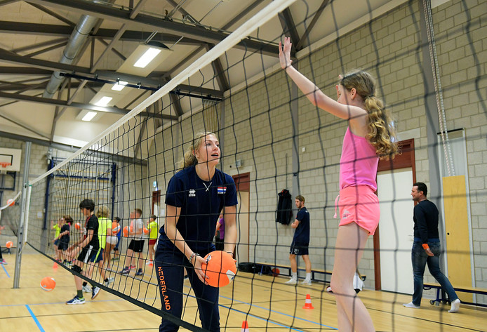 Mirte van der Sluijs geeft een leerlinge van de Beatrixschool uitleg over de volleybalsport.
