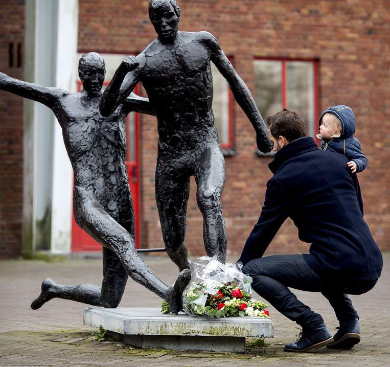 Een man legt bloemen bij het standbeeld van Johan Cruijff naast het Olympisch Stadion Beeld anp