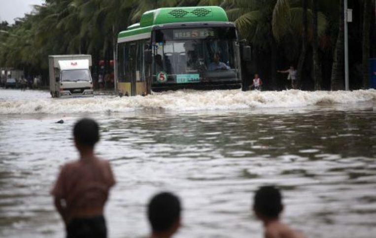 Hainanezen kijken naar hun overgestroomde straat. ANP Beeld