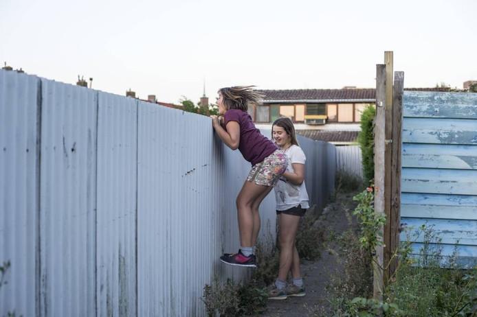 Tara van Os (links) springt om in een brandgang over de schutting te kunnen kijken voor boeven.