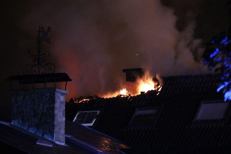 De vlammen sloegen uit het dak bij aankomst van de brandweer.