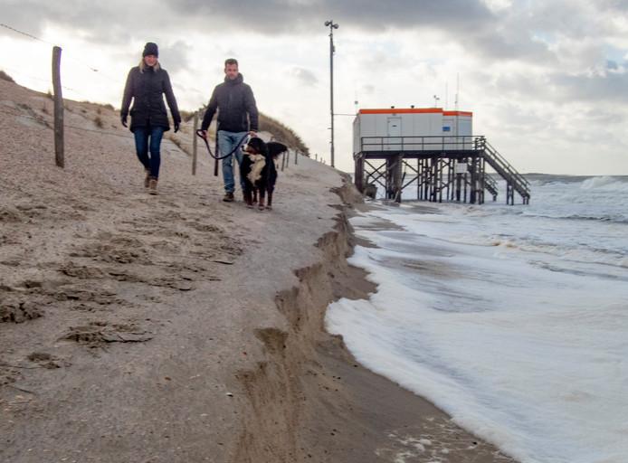 Tim Sinke en Marjolein van Vliet met hond Hazel kunnen niet verder op het Banjaardstrand bij de reddingspost door het afgeslagen strand en hoog water.